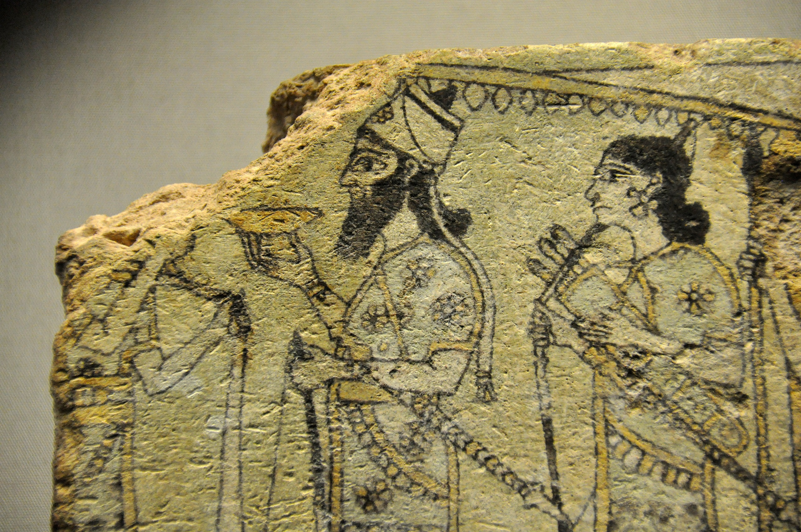 This detail of a glazed terracotta tile from Nimrud, Iraq, illustrates the Assyrian king below a vast parasol borne by attendants, c.875-850 BC [Wikimedia Commons]