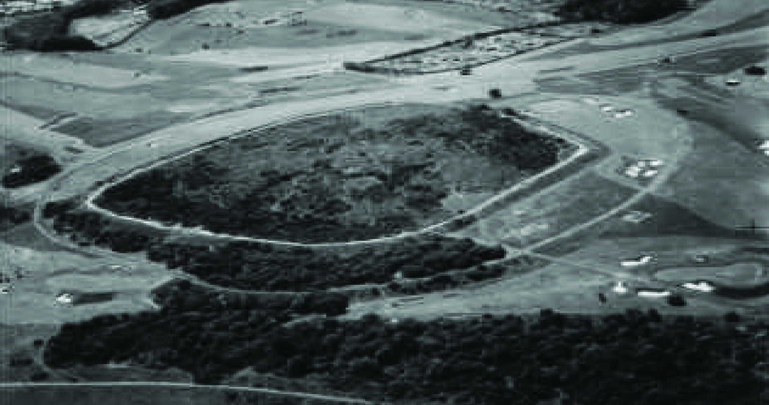 An aerial view of Hollingbury Camp, showing features of the Iron Age hill fort and of the surrounding landscape. Dating from the sixth century to about the middle of the second century BCE, it is a scheduled ancient monument, covering about 9 acres in a rough square about 600 feet across, with gateways to east and west through ramparts that can still be seen. The camp was excavated in 1908 by Herbert S. Toms, a Curator at Brighton Museum, by Cecil Curwen and Brighton and Hove Archaeological Society in 1931, and by John Holmes in 1967. The sites of some wooden huts have been discovered within the fort.